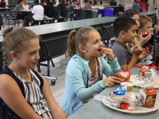 Students at Pinewood Elementary in Mims eat lunch Monday,