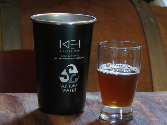 A taster of Kentucky common ale by homebrewer Ron Baran is seen with a souvenir metal cup during the Pure InFATuation Brew Competition in Oxnard.
