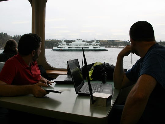 Jeff Coughlin, left, and Arthur Bogard watch as the Chimacum passes their vantage point from the Kaleetan in Rich Passage. The two scientists tested cell service on both vessels Friday, finding much weaker levels aboard the Chimacum.