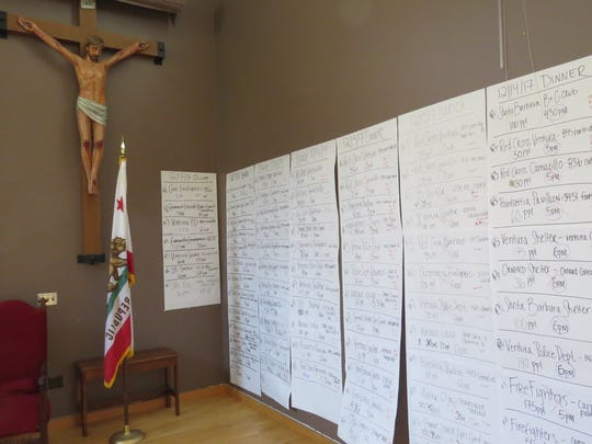 Sheets of paper taped to the walls of O'Brien Hall at San Buenaventura Mission in Ventura help keep track of the thousand of meals prepared daily by World Central Kitchen for Thomas Fire evacuees and first responders.