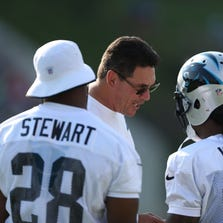 Ron Rivera talks with running back Jonathan Stewart (28) and running back DeAngelo Williams (34) during training camp at Gobbs Stadium.