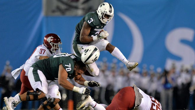 Michigan State Spartans running back LJ Scott (3) knocks the helmet of guard Tyler Higby (70) off as he leaps over the pile as Washington State Cougars linebacker Justus Rogers (37) defends during the second quarter in the 2017 Holiday Bowl at SDCCU Stadium.