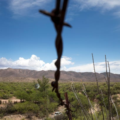 A barbed-wire fence separates the members of the Tohono