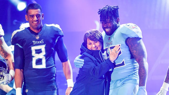 Titans owner Amy Adams Strunk hugs Tennessee Titans tight end Delanie Walker (82) next to quarterback Marcus Mariota (8) during the Titans uniform reveal event held at Broadway and 1st Avenue in Nashville, Tenn., Wednesday, April 4, 2018.