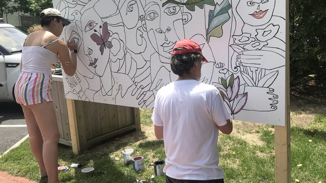 Emma and Richard Tichnor paint a portion of the community mural designed by Jackie Reeves and set up at the Cultural Center of Cape Cod in South Yarmouth.