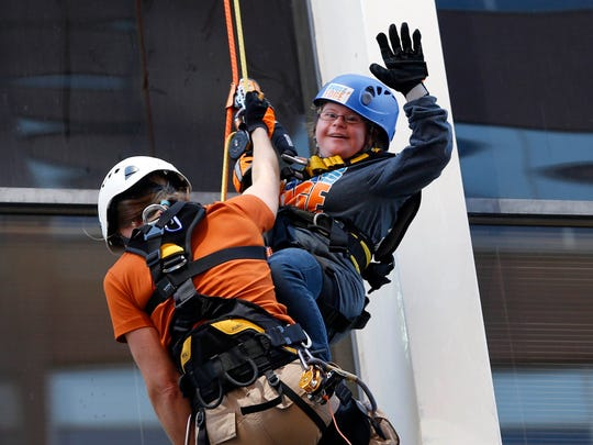 Angela Oberlander waves to the crowd on the ground Wednesday, Sept. 16, 2015, as she and Sara Kreps complete a tandem rappel down the side of The Financial Center during the Over the Edge fundraiser for Special Olympics Iowa.