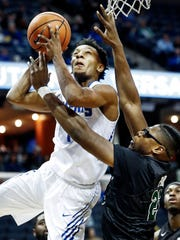 Memphis guard Jamal Johnson (left) drives to the basket against Tulane defender Blake Paul (right) during first half action at the FedExForum in Memphis Tenn., Tuesday, January 9, 2017.