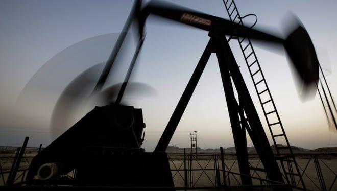 An oil pump works at sunset in the desert oil fields of Sakhir, Bahrain.
