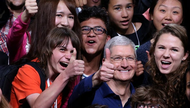 Apple CEO Tim Cook (center) poses for a photo with high school kids during Apple WWDC on June 8, 2015 in San Francisco.