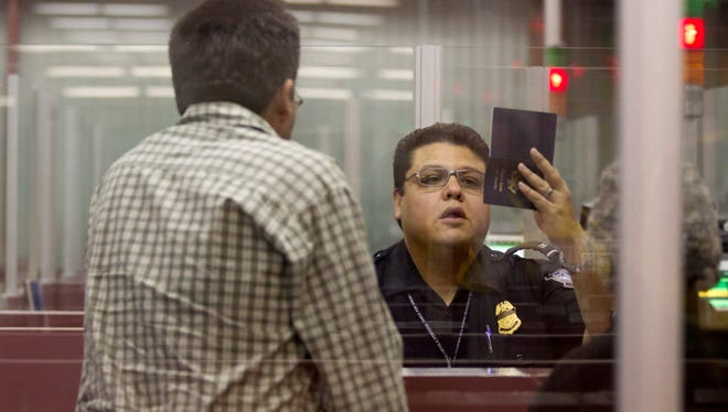 A customs officer checks the passport of a non-resident visitor to the United States at the Las Vegas airport in 2011.