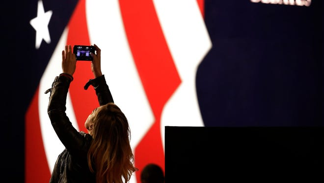 Lena Gjokaj takes a cellphone photo of the stage for the presidential debate between Democratic presidential candidate Hillary Clinton and Republican presidential candidate Donald Trump, at Hofstra University in Hempstead, N.Y., Monday, Sept. 26, 2016.