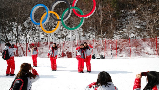 Volunteers take photos in front of the Olympic rings near the finish area during men's downhill training at the 2018 Winter Olympics in Jeongseon, South Korea, Friday, Feb. 9, 2018.