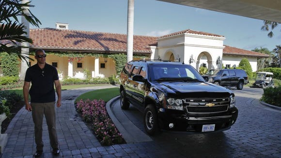 A U.S. Secret Service Agent stands near vehicles from
