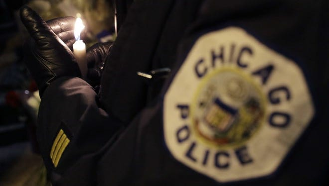 A Chicago police officer shields their candle from the wind as they attend a candlelight vigil for police Cmdr. Paul Bauer outside the Near North District headquarters Wednesday, Feb. 14, 2018, in Chicago.