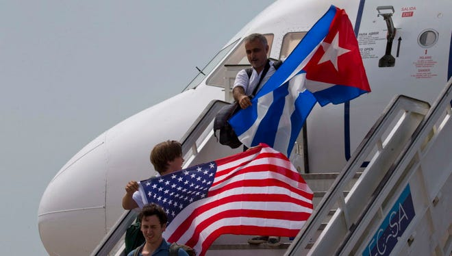 Two passengers deplane from JetBlue Airways flight 387 waving a United States, and Cuban national flag, in Santa Clara.