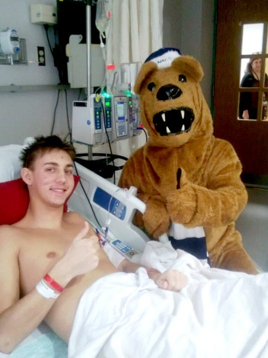 Brandon Hohenadel is shown in his bed in December at the Hershey Medical Center, posing with the Nittany Lion. (SUBMITTED)