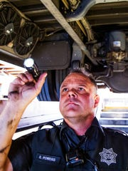 Department of Public Safety Trooper Steve Powers inspects a Gilbert Public School bus on April 14, 2016.