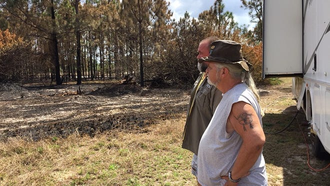 Terry Stout and John Doudna check out how close a fire came to an RV on Sunday. The in-laws were visiting relatives in Lehigh Acres when the fire, started by children, quickly spread.