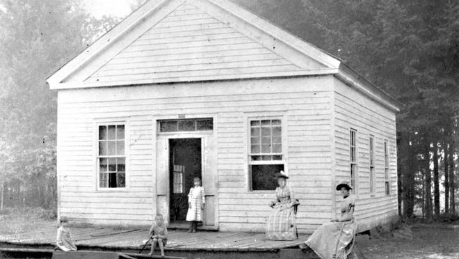 Two adults and three children are seen in front of Pringle School in 1891. The building was replaced in 1896.