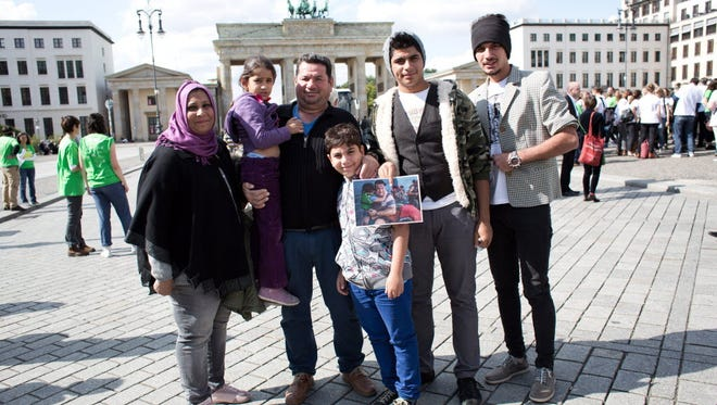 A Syrian refugee family poses in front of the Brandenburg gate in Berlin on Sept. 10, 2015.