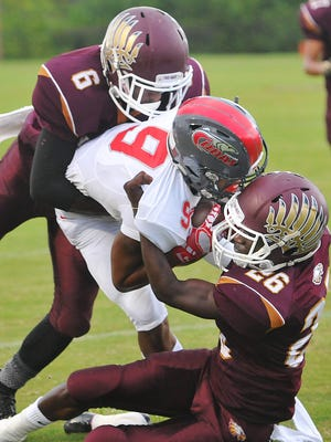 Astronaut high's defenders Simon Anderson (6) and Quantay Byrom take down a New Smyrna runner in the season opener.