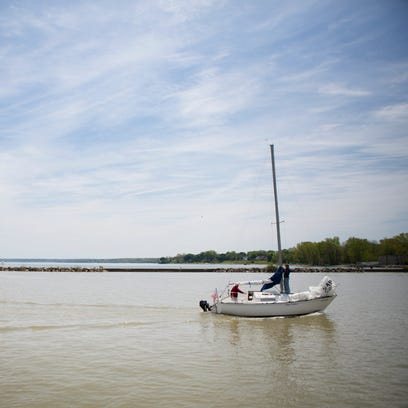 A boat enters Genesee River from Lake Ontario on Sunday