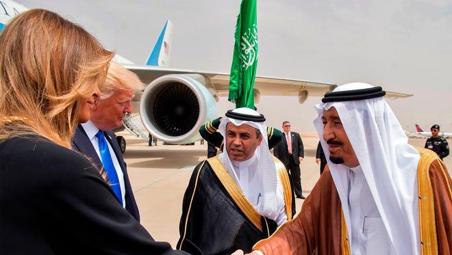 First lady Melania Trump shakes hands with Saudi King Salman bin Abdulaziz al-Saud upon arrival at King Khalid International Airport in Riyadh on May 20, 2017.