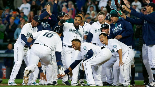 Seattle Mariners' Dae-Ho Lee (10) is greeted at the plate by teammates after he hit a walk-off two-run home run in the tenth inning of a baseball game against the Texas Rangers, Wednesday, April 13, 2016, in Seattle. The Mariners beat the Rangers 4-2 in ten innings.