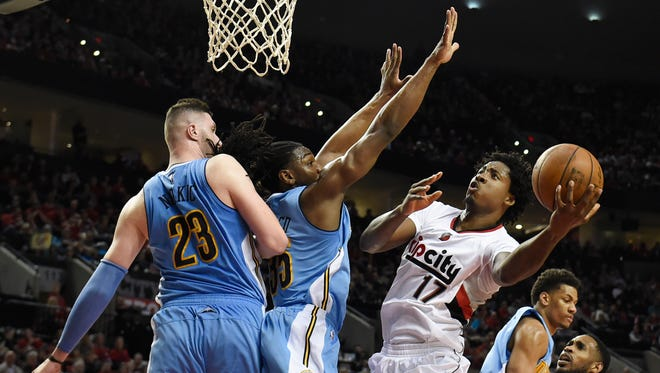 Portland Trail Blazers center Ed Davis (17) drives to the basket on Denver Nuggets center Jusuf Nurkic (23) and forward Kenneth Faried during the second half of an NBA basketball game in Portland, Ore., Wednesday, April 13, 2016. The Blazers won 107-99.