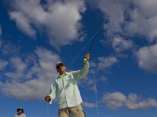 Writer Jack Ballard, of Red Lodge, Montana, casts out his fly-fishing rod Wednesday afternoon in Pine Island Sound as boat captain Ozzie Lessinger looks on from the boat's deck. Ballard was one of the members of the Outdoor Writers Association of America which met on Captiva. The group was participating in a saltwater fly-fishing outing put together by members of the Lee County Visitor and Convention Bureau.