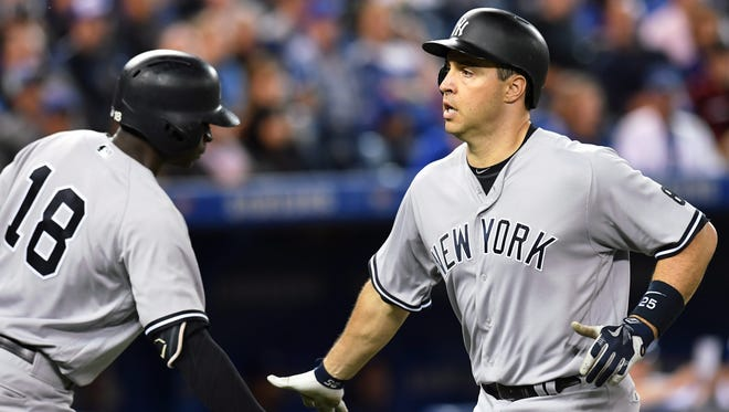 New York Yankees' Mark Teixeira is congratulated at home plate by teammate Didi Gregorius after rounding the bases on a home run during ninth inning of a baseball game against the Toronto Blue Jays on Monday, Sept. 26, 2016, in Toronto.