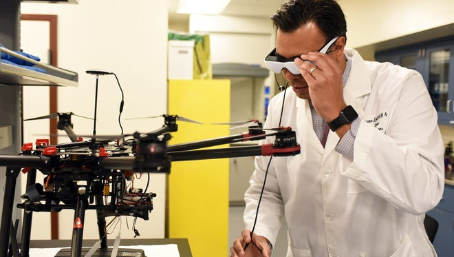 Italo Subbarao, a doctor with William Carey University's College of Osteopathic Medicine, demonstrates the navigating glasses for a telemedical drone in Hattiesburg. The drone is designed to carry an advanced medical kit to areas where emergency personnel may not be able to reach.