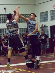 Shaun Perez, FDMS class of 2002, nails a shot over 2010's Josh Aglubat. Bradley Aflague, at rear, took a spill on the play. The combined class of 02-04 will take on the class of '06 at 8 p.m. July 14 at the FDMS Jungle