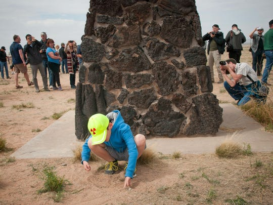 8-year-old Josiah Fidel, from Albuquerque, New Mexico plays in the dirt next to the obelisk commemorating the first atomic bomb test at the Trinity Site at White Sands Missile Range in New Mexico as other visitors to the site take photographs on April 4th, 2015. The White Sands Missile Range opened the Trinity Site to the public for an open house commemorating the 70th anniversary of the first atomic test which took place there on July 16th, 1945. Several thousand visitors came to see the site, take photographs and learn more about the event.