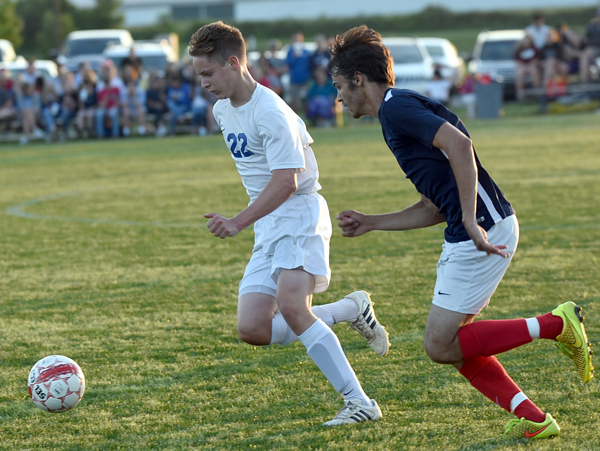 White House High sophomore defender Seth Bumbalough dribbles upfield as White House Heritage senior Trent Burian pursues during first-half action.