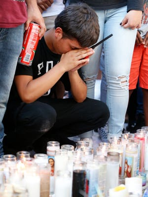 A mourner of rapper XXXTentacion pauses at a memorial, Tuesday, June 19, 2018, outside Riva Motorsports in Deerfield Beach, Fla., where the troubled singer was killed the day before.