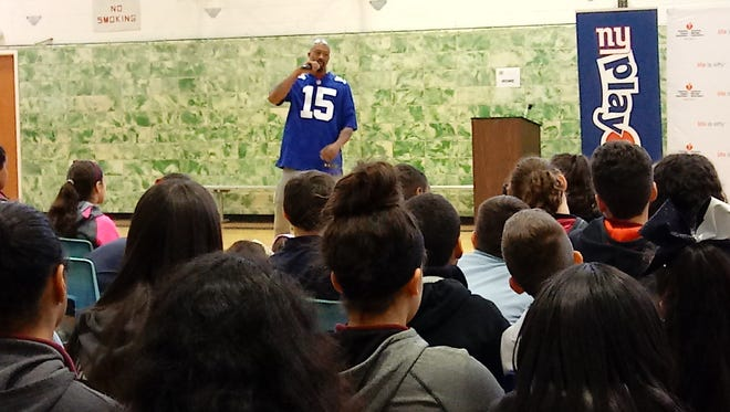 New York Giants Wide Receiver Tavarres King talks to sixth grade students at Memorial Middle School in Woodland Park Dec. 12 about the importance of being physically fit and living a healthy lifestyle. King and former Giants Wide Receiver Brandon London visited the school as part of the Play 60 Challenge, an initiative that encourages students to engage in physical activities for 60 minutes a day for four weeks. The National Football League (NFL) and the American Heart Association teamed up to create the Play 60 Challenge in an effort to curb childhood obesity. During the assembly, the children did squats and other exercises.