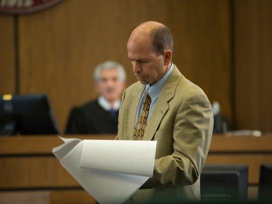 Defendant Jess R. Lilley reads over a transcript June