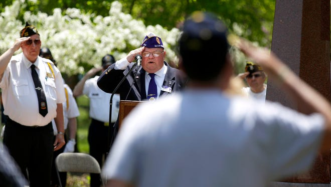 Cmdr. Dave Mix (left) and Roy Rogers of VFW Post 2126 are joined by members of the audience as they salute during the ceremony as Armed Forces Day is celebrated at the Isle of Valor near Smith Park on Saturday in Menasha. Branches of the armed services took part in the event as the isle was designated a state historical site.