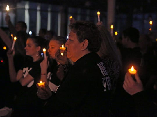 Alicia Gutierrez holds a candle during a vigil to honor Brandon Ellingson on Sunday at Valley High School in West Des Moines. Ellingson drowned in May after going out of a boat with his hands cuffed behind his back while in the custody of Missouri law enforcement. Sunday would have been his 21st birthday.