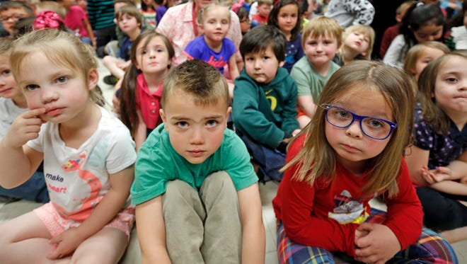 Students from the Meadowbrook Elementary School watch as Utah Gov. Gary Herbert signs a bill at the Meadowbrook Elementary School Monday, April 16, 2018, in Bountiful, Utah. Herbert signed the bill creating a path to raise education funding in a deal lawmakers reached with a well-connected group of business, political and education leaders. (AP Photo/Rick Bowmer)