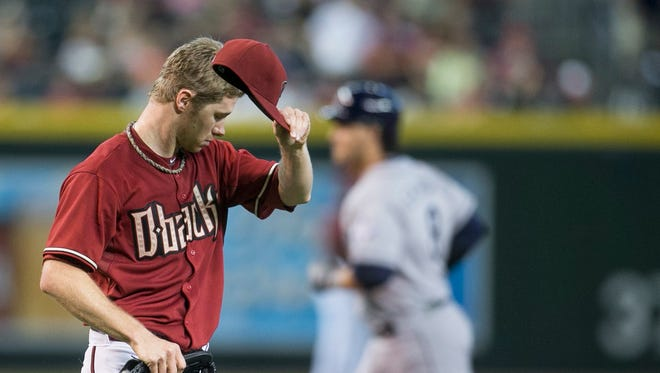Diamondbacks' Chase Anderson wipes his forehead after allowing a three-run home run to Padres' Yasmani Grandal in the fifth inning at Chase Field in Phoenix, AZ on Sunday, August 24, 2014.