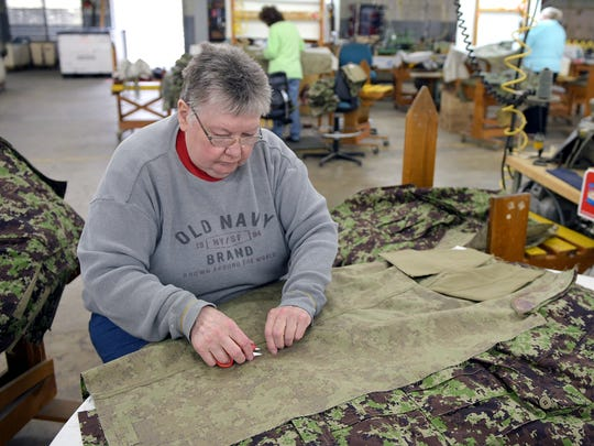 Shirley McCormick cuts the loose threads on military pants for the U.S. government Thursday at her job at Racoe Inc., in Celina, Tenn. McCormick used to work for Oshkosh, which employed 600 people working three shifts, before its Celina plant closed in 1996.
