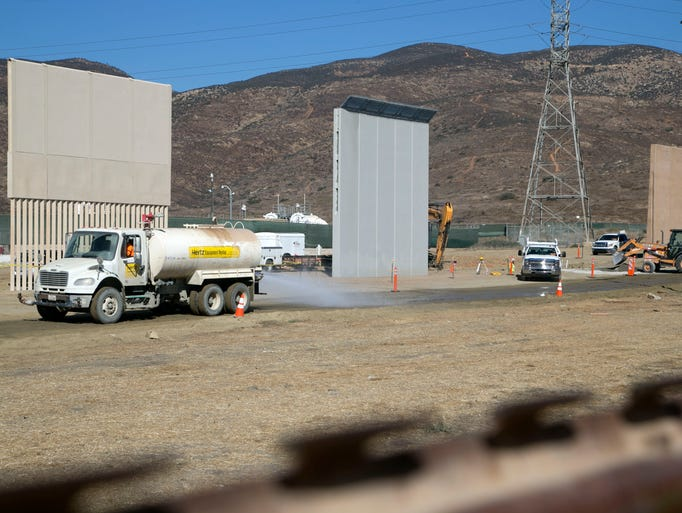Three border wall prototypes are seen among the construction