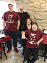 The new Carl's Pizza Kitchen in the village of Webster is a dream come true for owner Carl Prinzing and his family. Here Carl (in back) with his son David, wife Malinda and daughter Alyssa.
