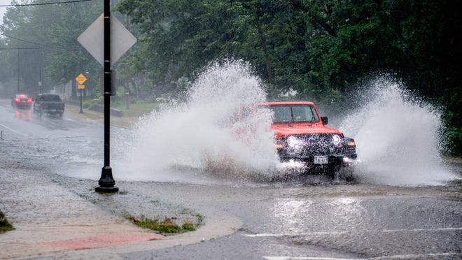 A Jeep splashes through the flooded intersection of N. North Street and W. Forrest Hill Avenueduring a heavy downpour Wednesday, July 15, 2020 in Peoria.