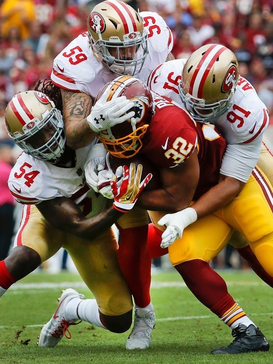 Washington Redskins running back Samaje Perine (32) is stopped by San Francisco 49ers outside linebacker Ray-Ray Armstrong (54), defensive end Aaron Lynch (59) and defensive end Arik Armstead (91) during the first half of an NFL football game in Landover, Md., Sunday, Oct. 15, 2017. (AP Photo/Alex Brandon)