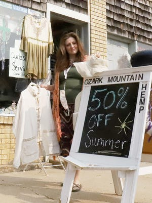 """Mondria Hamilon, Ozark Mountain Hemp owner, sets out a hemp chi jacket and matching hat to display in front of her """"old downtown,"""" storefront, 513 Main St, Friday, Sept. 18, in Van Buren."""