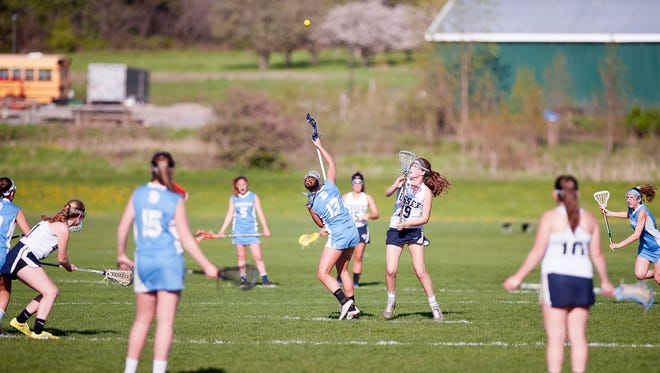 South Burlington's Annika Nielsen (13) and Essex's Olivia Miller-Johnson vy for control of the draw during a high school girls lacrosse game in Essex.
