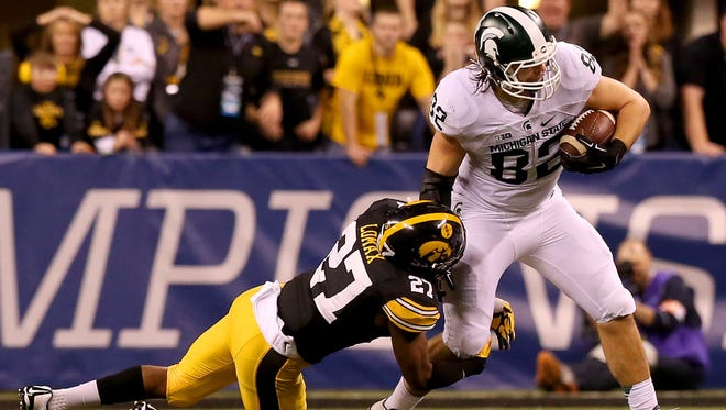 Michigan State tight end Josiah Price (82) breaks a tackle by Iowa defensive back Jordan Lomax (27) during the Big Ten Championship Game at Lucas Oil Stadium on Dec. 5, 2015.
